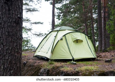 Green tent in forest, camping. Tourism, lifestyle, activity