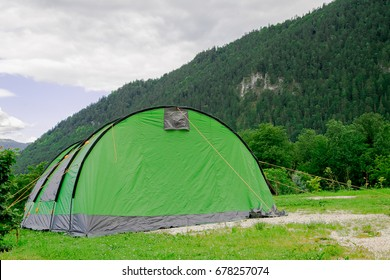 Green tent with mountain background on summer holidays