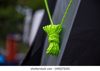 Green tent nylon strap. Rope with knot. Detail of a tent.