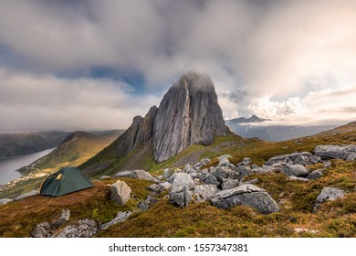Green tent on mountain ridge over clouds adventure journey traveling outdoor in Norway active vacations sunset Segla mountain, Senja.