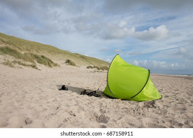 green tent on sandy beach with cloudy sky and dunes