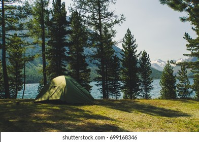 A green tent in the woods in the background a beautiful lake. Camping and tent under the pine forest. Tourists camped in the woods on the shore of the lake on the hillside