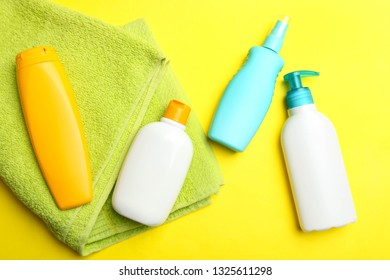 Green terry towel and plastic bottles on bright yellow background. Concept hygiene, body care. Top view