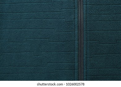 Green textile with zipper closeup. Green textile texture. Copy space on green textile background.