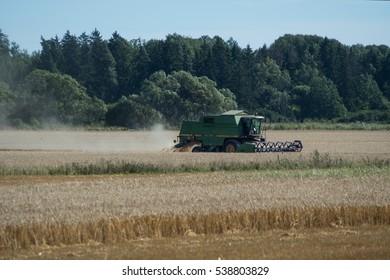 Green threshing machine in action, harvesting the fields of grain. Irsta, Sweden, 2016-08-27