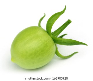 Green tomato over white background with selective focus