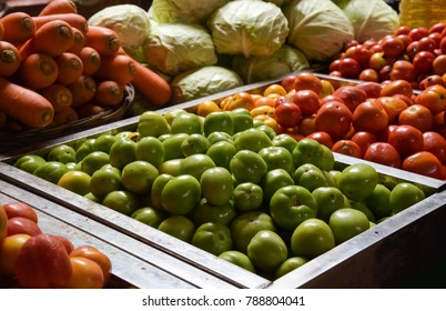 Green tomatoes at fresh market, surrounded by another vegetables