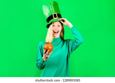 Green top hat. Blonde girl in Leprechaun costume holds pot with gold. Leprechaun. Pot with gold. Green leprechaun. Green hat with clover. Saint Patrick's Day. Traditions of Saint Patrick Day.