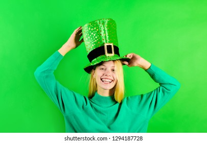 Green top hat. Blonde girl in in green top hat holds pot with gold. Green leprechaun. Green hat with clover. Traditions of Saint Patrick Day. Leprechaun costume.