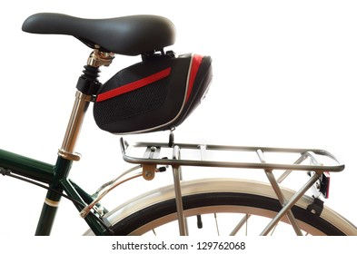 Green touring bicycle saddle and pannier rack isolated on a white background