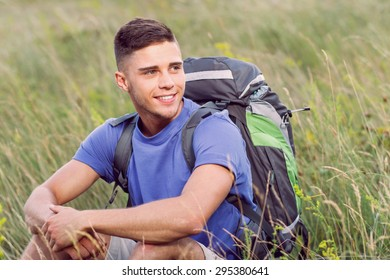 Green tourism.  Portrait of a young handsome tourist wearing blue t-short and beige shorts, sitting on the plaid wearing backpack looking aside smiling