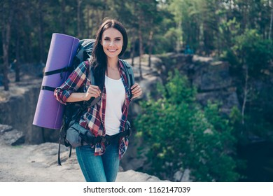 Green tourism. Trendy stylish nice lovely cute girl on vacation, traveling, spending free spare time on fresh air in wild wood on top of rock near water, wandering, exploring the world