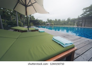 Green Towel on the sun bed near swimming pool. Vintage tone