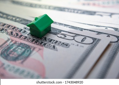 The green toy house placed on top of 50 US dollar banknotes. Macro photo. Concept image for mortgage and house market. Selective focus.