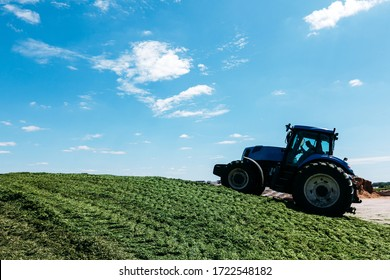 green tractor on a mountain of granulated alfalfa stored in the production of feed for farm animals during the day