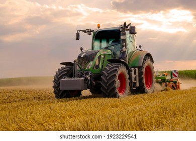 green tractor plowing cereal field with sky with clouds