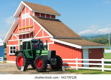 Green Tractor and Red Barn with blue sky and white fence.