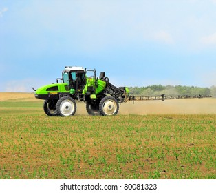 green tractor is spraying field