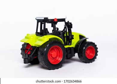 A green tractor toy car on a white background.it's small and cute.