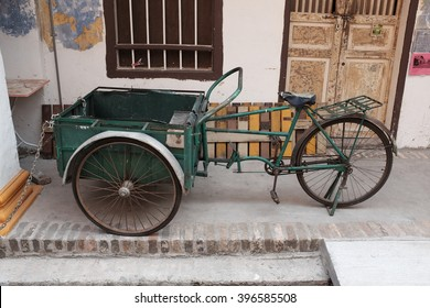 Green traditional trishaw in front of colonial building.