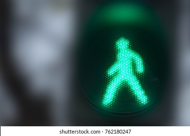 Green traffic light with a walking person symbol in the city street