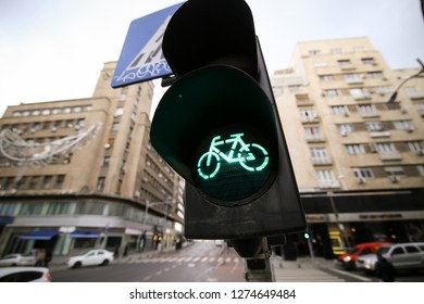 Green traffic lights for bikers on a city street and a crosswalk sign