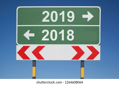 Green traffic sign with white letters and th arrows in different directions showing the numbers  2018 and 2019, concept fot turn of the year