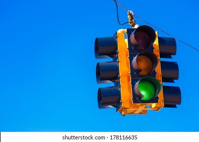 A green traffic signal with a sky blue background