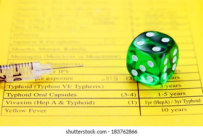 A green translucent dice, placed on a vaccination passport with a loaded syringe adjacent to it, asking the question, are your vaccinations up to date.