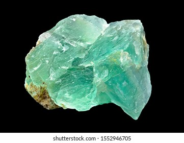 Green translucent fluorite rough mineral stone on a black background