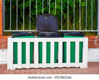 Green trash bins behind a white wooden fence stand outside in front of a fence with green plants behind it