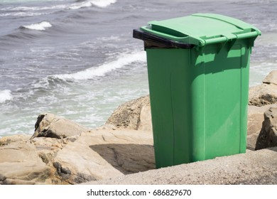 green trash can on the beach