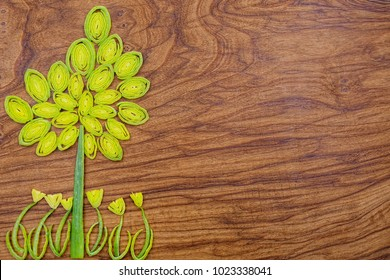 Green tree and flowers made of leek slices on wooden cutting board background with copy space for your text. Vegetarian diet, funny healthy eating, creative cooking concept.
