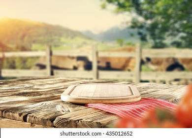 green trees and farm and shabby wooden table and red napkin and red vegetables