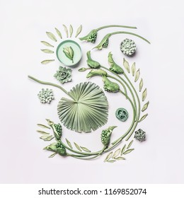 Green tropical leaves and curl flowers composition with water bowl on white background, top view, flat lay. Spa and wellness, concept with copy space for your design, text or product