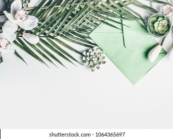 Green Tropical leaves with orchid flowers, envelope, and succulent decoration on white desktop background, top view, border