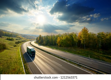 Green truck driving on the asphalt highway between deciduous forest in autumn colors under the radiant sun and dramatic clouds. View from above.