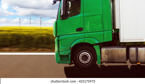 green truck in front of canola field with wind wheels and cloudy sky