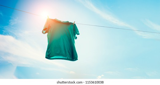 Green t-shirt on clothes line against sun and blue sky with clouds.