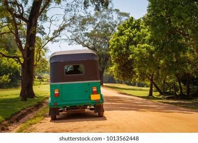 Green tuk tuk on the sand road, Sri Lanka