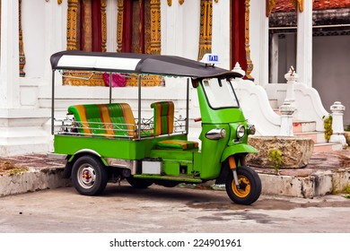 the green tuk tuk at temple in thailand,three wheel