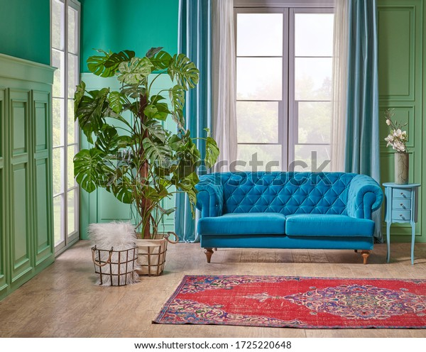 Green turquoise wall background, white window and blue sofa interior design.