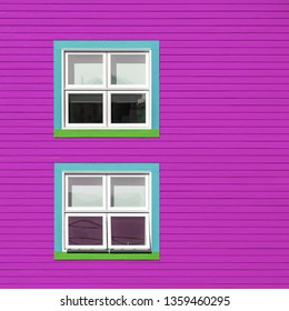 Green, turquoise and white windows on a pink wooden wall. Minimalism style of the houses of Iles de la Magdalen, Canada, in bright colours with space for text.