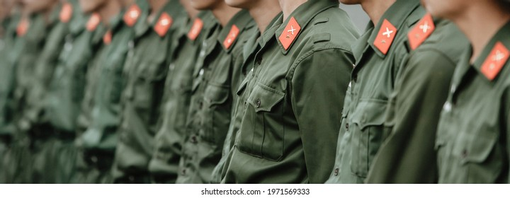Green uniform of Vietnamese soldier. Red star and cross swords icon in ribbons on shoulder. Young Vietnamese soldiers in a row during site visit program. Dien Bien Phu, Vietnam. Selective focus.