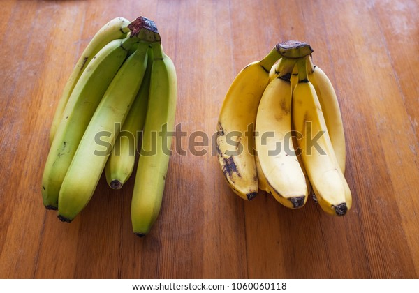 Green unripe with yellow ripe mature bananas, ripening process concept, on a wooden desk or table or board