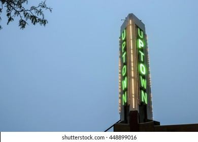 Green Uptown Neon Sign Against A Cloudy Blue Dusk Sky