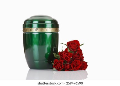 Green urn and red roses on white background