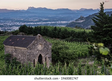 Green Rhône valley Cornas vineyard with old stone chapel on the foreground, Crussol castle dominating Valence city and high mountains on the background.