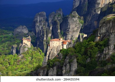 Green valley and Greek monasteries surrounded by dark cliffs, Meteora, Greece