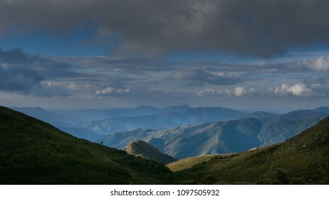 A green valley with just a tiny sun light and in the background, beautiful mountains and blue sky